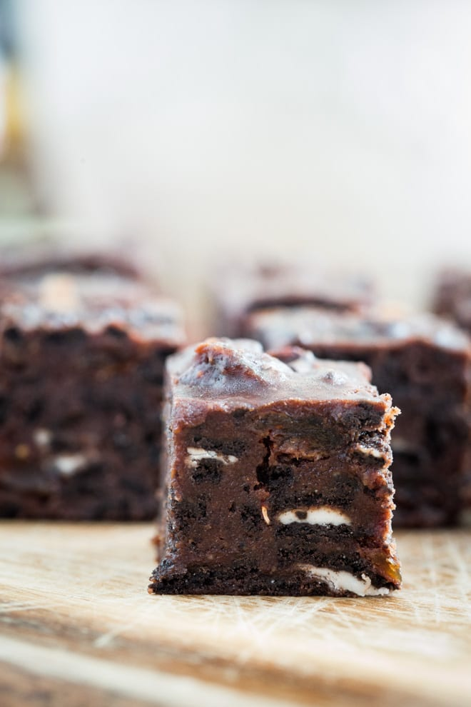 Vegan Chocolate Tiffin - crushed Oreos, dried fruits, golden syrup, rich dark chocolate and peanut butter all crammed into this festive treat! #veganchristmas #veganchocolate   Recipe on thecookandhim.com