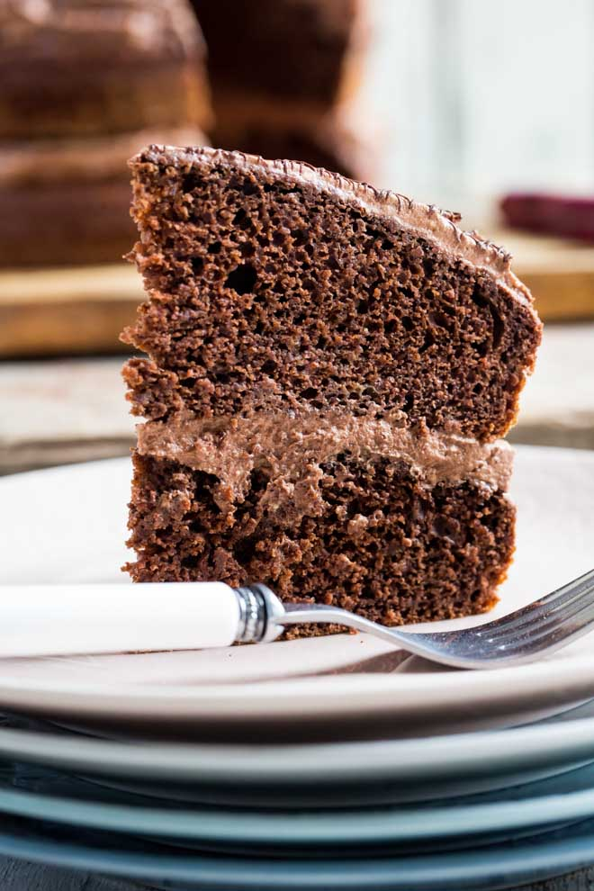 The yummiest Vegan Chocolate Fudge Cake, rich but light and divinely chocolatey with a creamy and fluffy vegan chocolate frosting #vegancake #veganchocolatecake #chocolatefudgecake #veganbaking | Recipe on thecookandhim.com