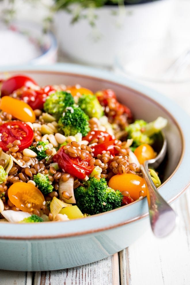Wheat Berry Summer Salad - plump little wheat berries mixed with tonnes of veggies, herbs and a creamy lemon, garlic and tahini dressing #salad #saladdressing #summerrecipes #healthysalad   Recipe on thecookandhim.com