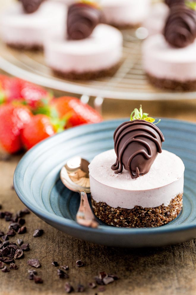 Raw, vegan and gluten free these mini strawberry cheesecakes with a nut and chocolate base are smooth, creamy and so easy to make! #vegandesserts #vegancheesecake #rawvegan #glutenfree | Recipe on thecookandhim.com
