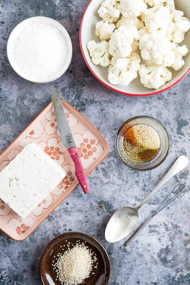 Crispy baked za'atar tofu and cauliflower, gently spiced and full of flavour. Drizzle with a creamy vegan tzatziki sauce for a quick and easy weeknight meal! #tofurecipes #cauliflowerrecipes #veganrecipes #veganmeal   Recipe on thecookandhim.com