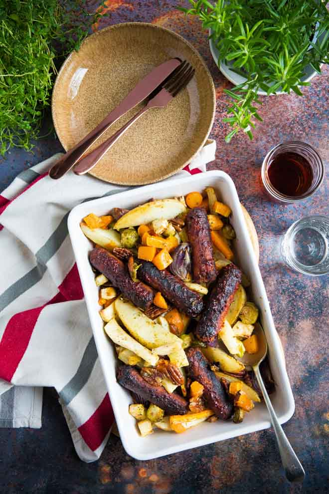 This tray bake is family friendly total comfort food - all cooked in one dish and perfectly adaptable to your own favourite sausages and veg! #traybake #sheetpanmeal #vegansausages #familymeal #roastveg   Recipe on thecookandhim.com