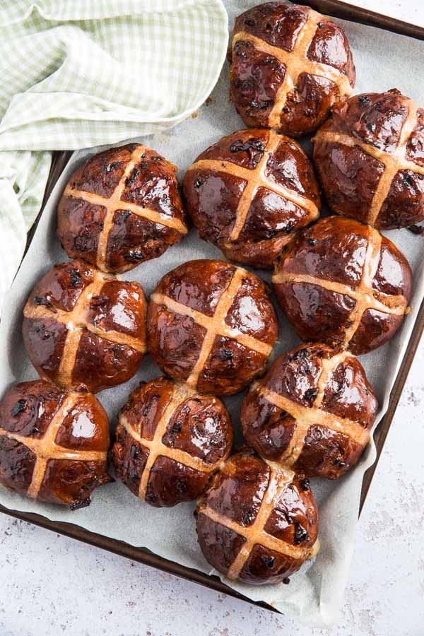 Celebrate Easter in style with these heavenly Double Chocolate and Orange Hot Cross Buns! Packed with zesty orange, chocolate chunks and soft apricots! #veganeaster #easterrecipes #veganchocolate #veganbaking #hotcrossbuns | Recipe on thecookandhim.com