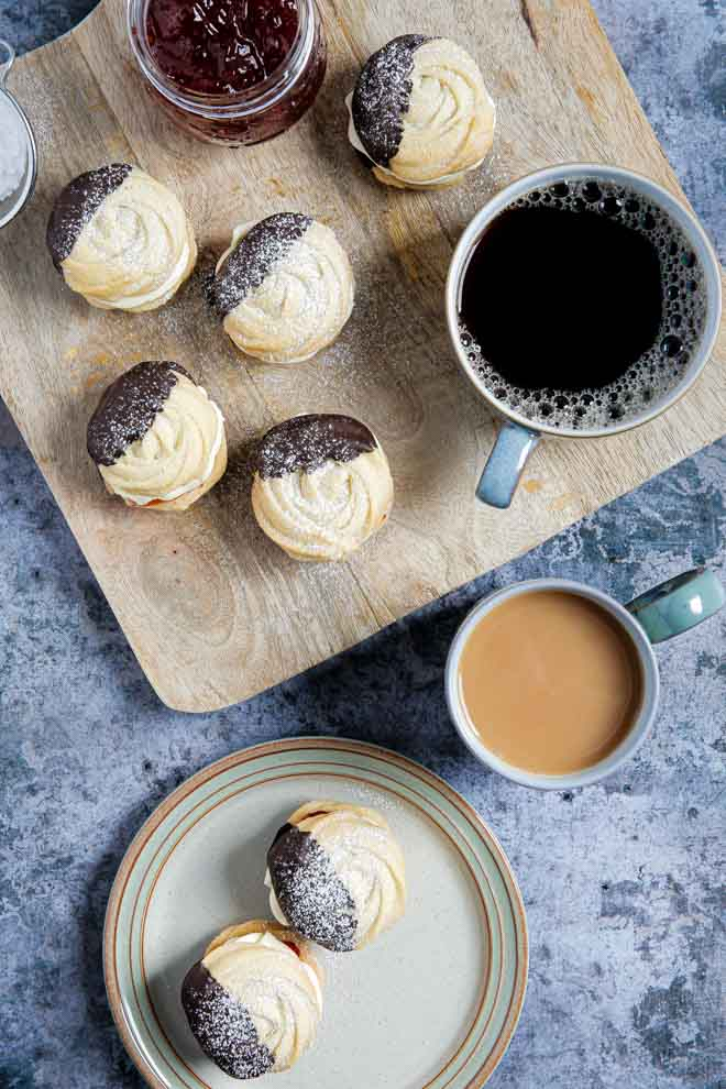 Light buttery vegan viennese whirls, dipped in dark chocolate and sandwiched with jam and buttercream. The perfect afternoon treat! #vegancookies #veganbaking #viennesewhirls #veganrecipe #butterbiscuits #howtomakeviennesewhirls | Recipe on thecookandhim.com