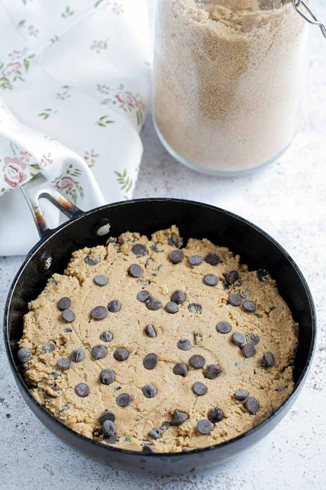 Warm, gooey and delicious this vegan chocolate chip skillet cookie is easily made in advance, baked fresh and a real crowd favourite! #skilletcookie #vegancookie #pizookie #veganrecipes #veganbaking #dairyfree   Reipe on thecookandhim.com