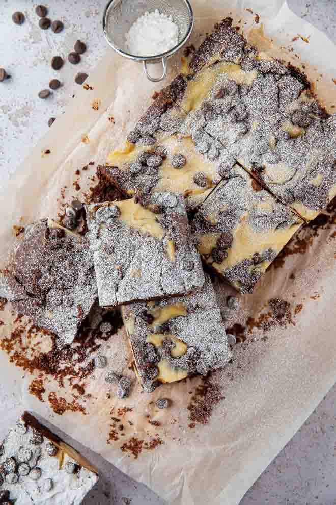 Rich, chocolatey and fudgy cheesecake brownies gently flavoured with blackcurrant and studded with dark chocolate chips. Decadently delicious! #veganbrownies #cheesecakebrownies #vegancheesecakebrownies #vegancheesecake #veganbaking #eggfree #brownies #creamcheesebrownies | Recipe on thecookandhim.com