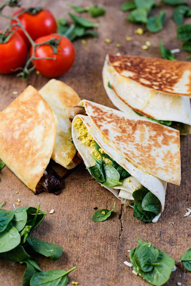 This folded breakfast wrap might not change your world but it'll definitely change the way you see folding wraps! This vegan breakfast version is filled with tofu eggs, vegan sausage, bacon and cheese, spinach and tomato. It's super easy, filling and SO delicious to eat! #breakfastwraps #veganbreakfast #vegansausages #veganbacon #tofuscramble #tofueggs #plantbased #highproteinveganbreakfast | Recipe on thecookandhim.com