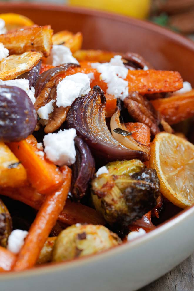 Vegan honey flavouring, caramelised lemon slices and fresh thyme give these roasted root veggies a delicious zesty tang! Top with crunchy pecans and vegan feta cheese and this dish becomes so much more than just a side! #veganhoney #roastveg #rootveg #sides #sidedishes #roastlemon | Recipe on thecookandhim.com