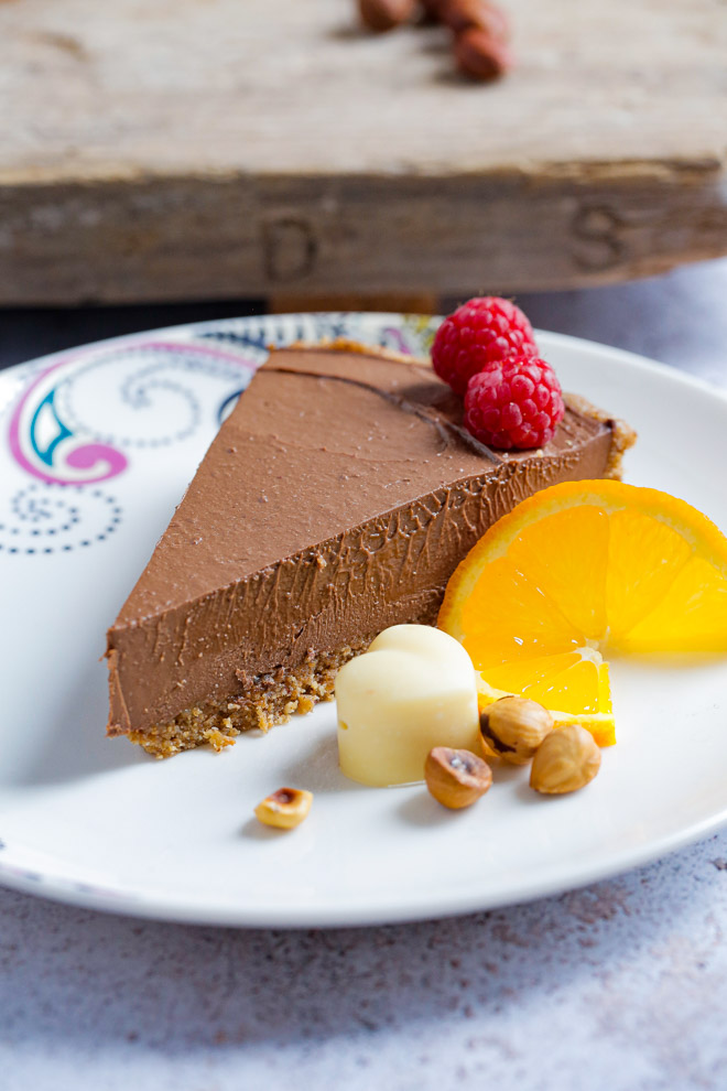 This decadent no bake chocolate tart really does taste as good as it looks! It has a nutty base and a rich smooth filling, all with a vegan protein boost! #vegan #nobake #chocolate #tart #homemade #veganprotein #plantbased #dairyfree | Recipe on thecookandhim.com