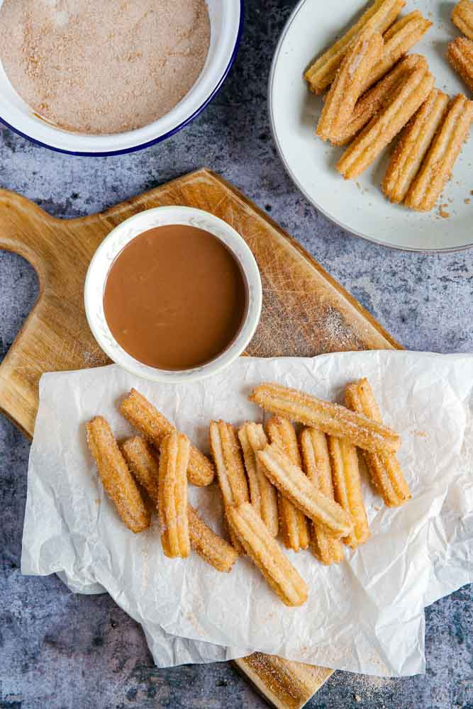 No one will ever know (or care!) that these caramel churros are vegan because they are SO good! Make sure to make a lot too, as they disappear FAST with their fluffy insides and cinnamon sugar crunchy outside! Dunk in velvety chocolate sauce for utter indulgence! #veganrecipes #vegan #veganchurros #churros #friedchurros #churrorecipe