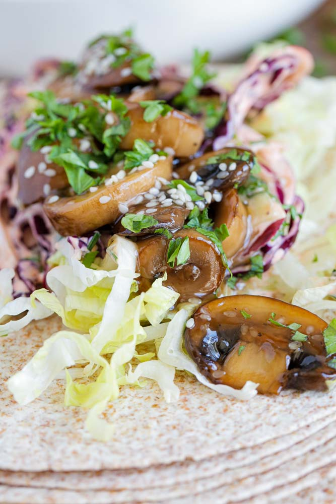Sticky, smokey and all the Asian teriyaki flavours are piled into these mushroom tacos with a base of creamy vegan red cabbage slaw. Delicious! #veganrecipes #vegan # plantbased #easyvegan #tacotuesday #tacos #vegantacos #teriyaki #mushrooms #veganslaw #vegancoleslaw   Recipe on thecookandhim.com