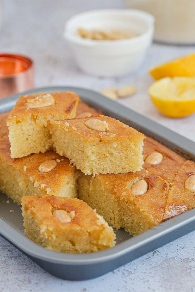 A traditional Middle Eastern cake make with a base of semolina and yoghurt, Basbousa is sweet, light and fragrant and so so moist! It's also studded with almonds and soaked after cooking in a sticky lemon syrup | Recipe on thecookandhim.com #basbousa #semolinacake #vegan #vegancake #eggfreecake #dairyfree #veganbaking