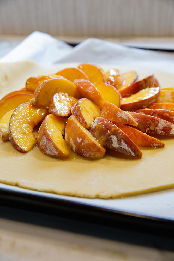 This easy, vegan peach tart is summer in every bite! Super simple homemade pasty brimming with fresh, juicy peaches served warm with a sweet orange and cardamom drizzle | recipe on thecookandhim.com | #vegan #vegandessert #peachtart #summertart #peaches #veganbaking #veganrecipe #veganpastry