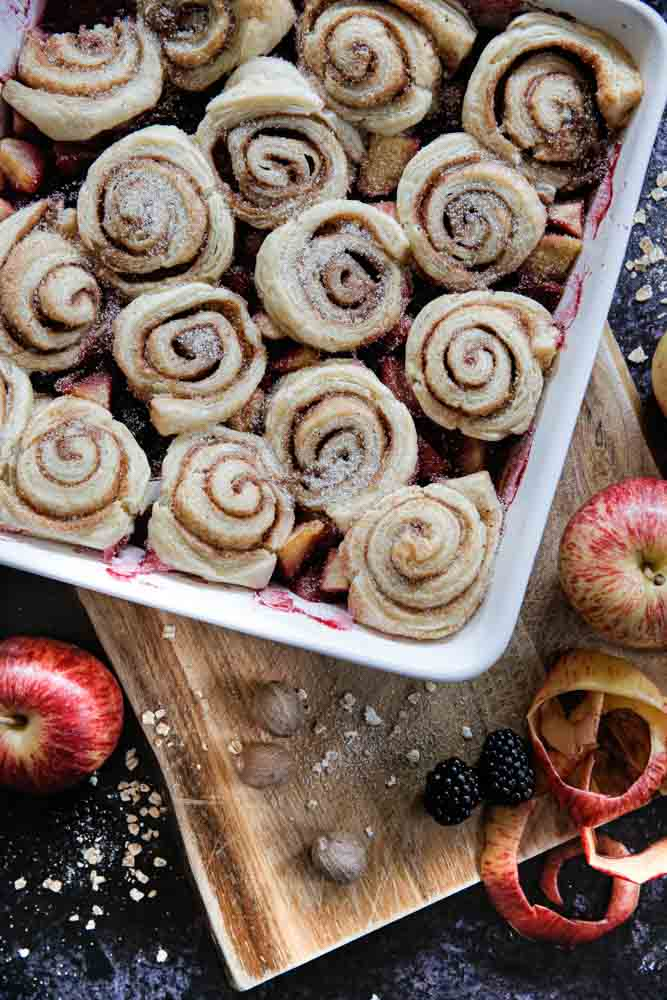 Brunch, breakfast or dessert this fruity apple and blackberry cobbler topped with crisp cinnamon rolls is full of sweet autumn flavour! Recipe on thecookandhim.com | #cinnamonrolls #veganrecipes #vegan #cobbler #appleandblackberry #autumnbrunch #autumndessert #fallfood #fallrecipe